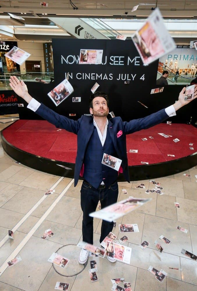 Magician Jamie Raven performs on stage, including giving away free money.